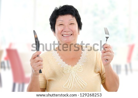 Happy Asian senior mother ready for her Mother's day meal, holding fork and knife inside restaurant. - stock photo