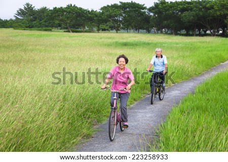 Happy asian seniors couple biking in the park.retirement and healthy lifestyle concept - stock photo