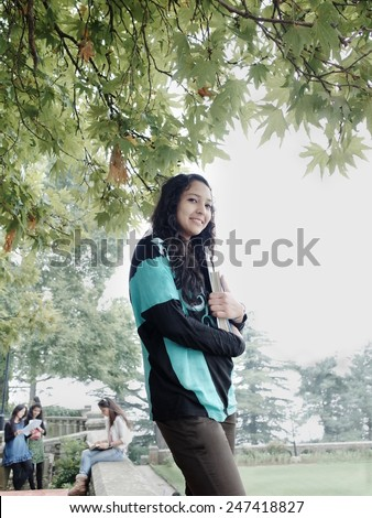 Happy asian teenager with books in university campus. - stock photo