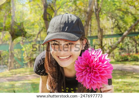 Happy Asian Thai young woman with pink dahlia flower blooming in the garden - stock photo
