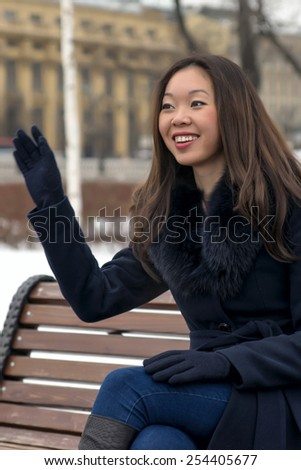 happy Asian woman a friendly wave of his hand - stock photo
