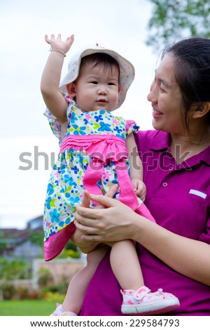 Happy asian woman and cute little girl relaxing at home back yard and bright sky background, mother carrying  her daughter - stock photo