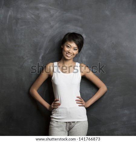 Happy Asian woman standing in front of a dark chalkboard. The chalk board is blank waiting for a message. - stock photo