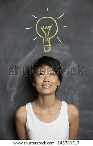Happy Asian woman standing in front of chalkboard with light bulb drawn above her head. Concept about ideas. - stock photo