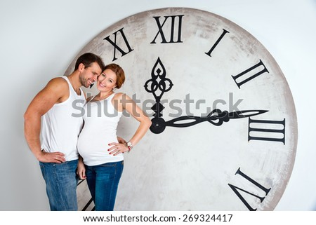 Happy athletic pregnant couple dressed in white on white background with giant clock. Time passing or a new life concept - stock photo