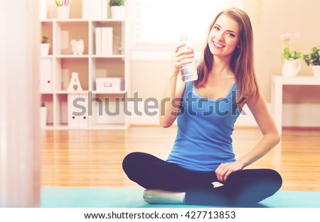 Happy athletic woman with a bottle of water in her home studio - stock photo