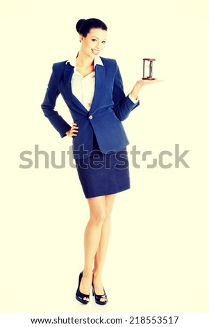 Happy attractive businesswoman with hourglass - time concept - stock photo