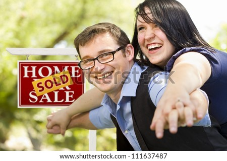 Happy Attractive Caucasian Couple in Front of Sold Real Estate Sign. - stock photo