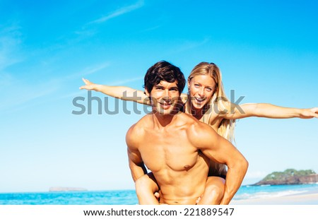 Happy Attractive Couple Playing and Having Fun on Beautiful Sunny Beach  - stock photo