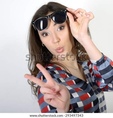 Happy attractive excited teen girl shows victory sign - stock photo