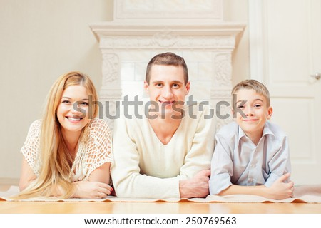Happy attractive family couple and son lying on the floor at home looking to camera - stock photo