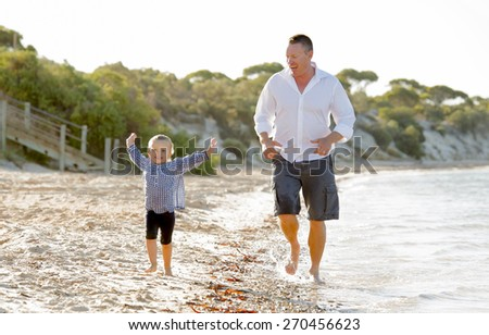 happy attractive father of sweet blond little girl playing and walking on water together with his excited laughing young daughter on beach sea shore on a sunny summer day - stock photo