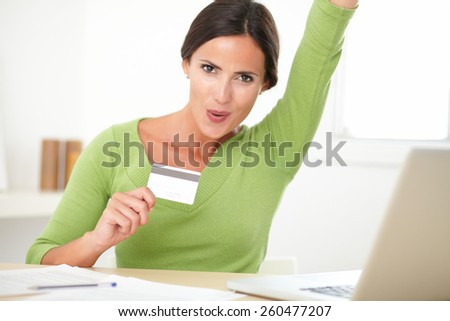 Happy attractive female in green shirt looking joyful on her desk while surfing the internet on the computer for shopping at home - stock photo