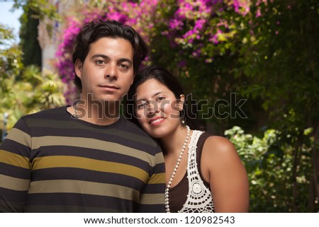 Happy Attractive Hispanic Couple Enjoying Themselves At The Park. - stock photo