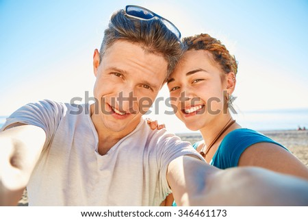 happy attractive man and woman looks into the camera on the sunny beach over the blue sky. Focus on the man - stock photo