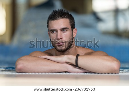 Happy Attractive Man Resting Relaxed On Edge Of Swimming Pool - stock photo