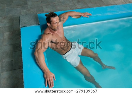 Happy Attractive Muscular Mature Man Resting Relaxed On Edge Of Swimming Pool - stock photo