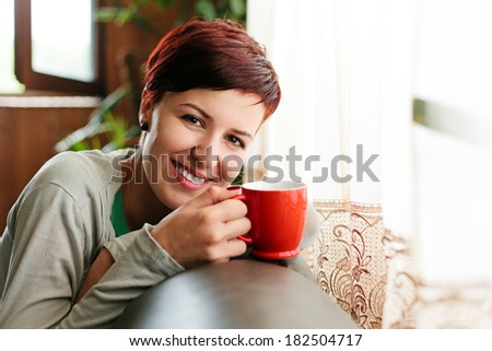 Happy attractive short haired woman with cup of coffee sitting on the sofa at home.. - stock photo