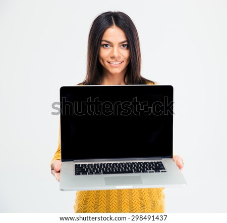 Happy attractive woman showing blank laptop computer screen over gray background. Looking at camera - stock photo