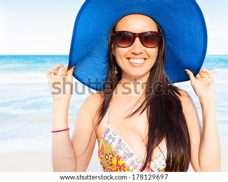Happy attractive woman smiling on the beach - stock photo