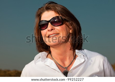 Happy attractive woman with sunglasses middle aged enjoying outdoors. Clear sunny spring day with blue sky. - stock photo