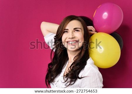 Happy attractive young birthday girl posing for a portrait holding colorful party balloons behind her head as she beams at the camera, over magenta - stock photo
