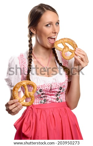Happy attractive young German or Bavarian woman in a dirndl eating pretzels holding two n her hands with her mouth wide open to take a bite, isolated on white - stock photo