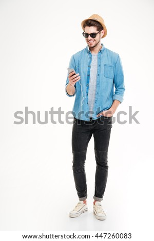 Happy attractive young man in hat and sunglasses listening to music from smartphone over white background - stock photo