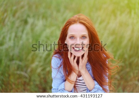 Happy attractive young redhead woman with a vivacious smile standing in a green grassy field smiling at the camera, close up view - stock photo