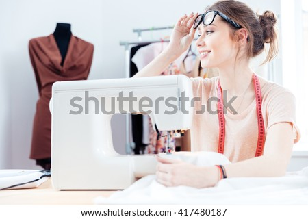 Happy attractive young woman seamstress sitting and sews on sewing machine in studio - stock photo