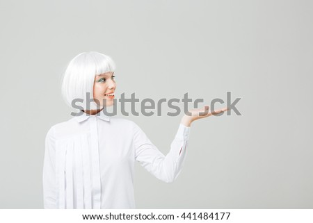 Happy attractive young woman with blonde hair holding copyspace on palm - stock photo