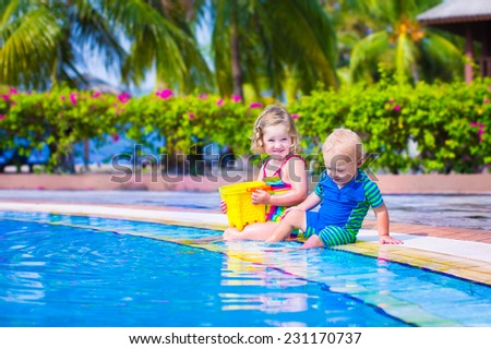 Happy baby boy and little curly toddler girl, brother and sister, playing with toy buckets and plastic shovel next to a swimming pool in a tropical resort with palm trees - stock photo