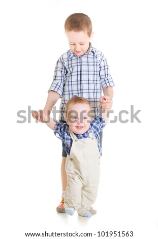 happy baby boy doing first steps with help of elder brother - stock photo