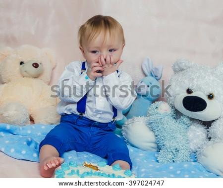 Happy baby boy eating cake by hands and feet for his first birthday party. Handsome little gentleman wearing the bow tie and suspenders. - stock photo