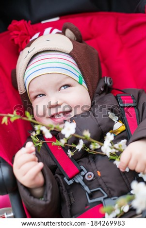happy baby boy in a stroller in a blossoming tree spring time - stock photo