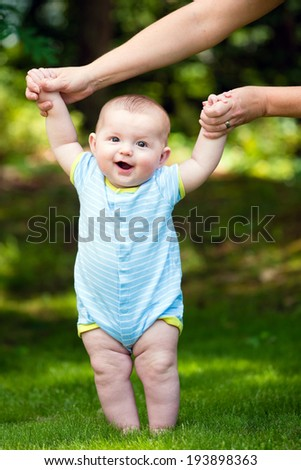 Happy baby boy learning to walk on grass outdoors - stock photo