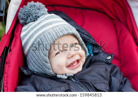 happy baby boy sitting in a red stroller for a walk - stock photo