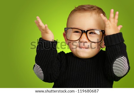 Happy Baby Boy Wearing Eye Glasses against a green background - stock photo
