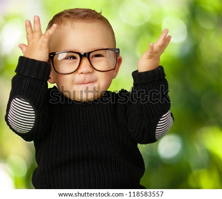 Happy Baby Boy Wearing Eye Glasses against a nature background - stock photo