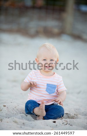 happy baby boy with blond hair and blue eyes in jeans and t-shirt sitting on the beach - stock photo