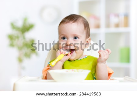 happy baby child sitting in chair with a spoon - stock photo