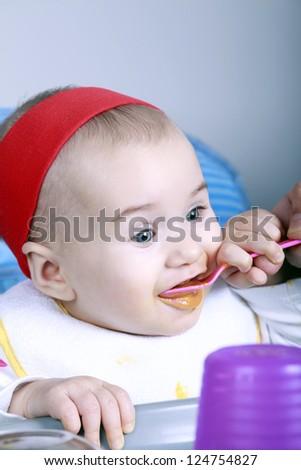 Happy baby eat with spoon - stock photo