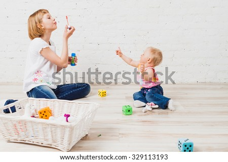 Happy baby girl catching bubbles which her older sister blowing - stock photo