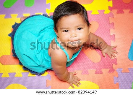 Happy baby girl crawling on a colorful play mat - stock photo