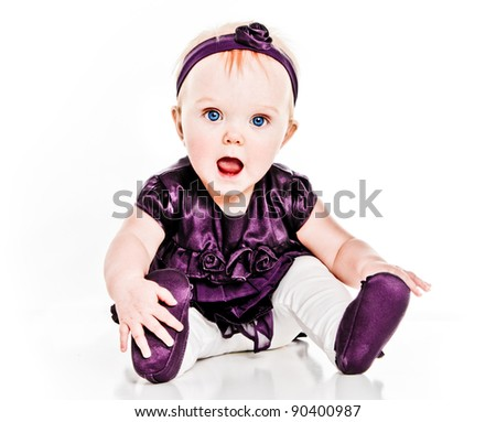 Happy Baby Girl excited playing with her feet in purple dress and shoes - stock photo