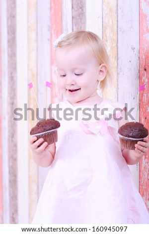 Happy baby girl holding two cupcakes - stock photo