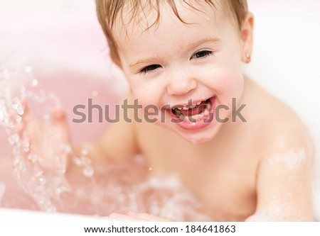 happy baby girl laughing and bathed in the bath - stock photo