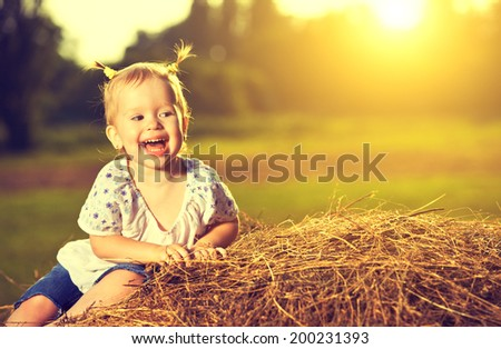 happy baby girl laughing on hay in summer at sunset - stock photo