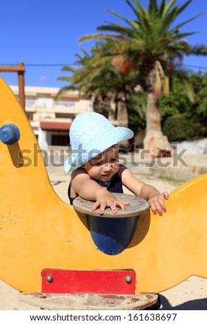 Happy Baby Girl playing in swing in the playground - stock photo