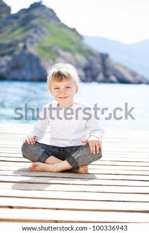Happy baby girl sitting on berth in summer - stock photo